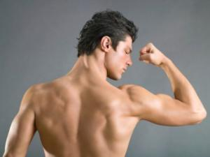 Rear view of man flexing biceps